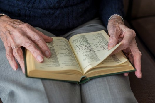elderly hands holding book