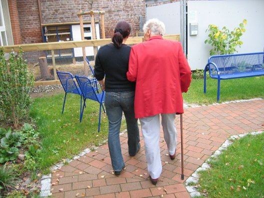 woman accompanying elderly on walk