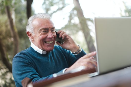 elderly man pointing to laptop laughing