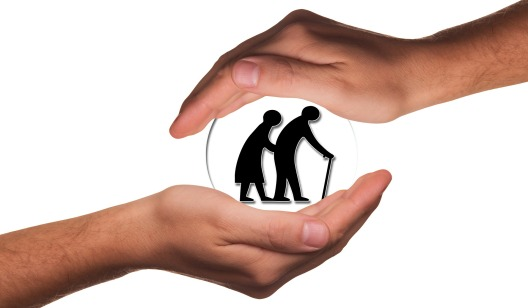 hands cradling image of elderly couple in sphere