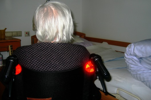 white haired man sitting in wheelchair by bed